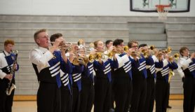 high school trumpet players in marching band uniforms